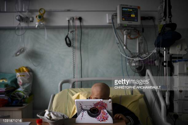 Six-year-old cancer patient watches cartoons on a tablet in his room at the paediatric oncology unit of the AP-HP Armand Trousseau hospital in Paris...