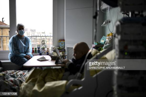 Six-year-old cancer patient watches cartoons on a tablet in his room next to his mother at the paediatric oncology unit of the AP-HP Armand Trousseau...