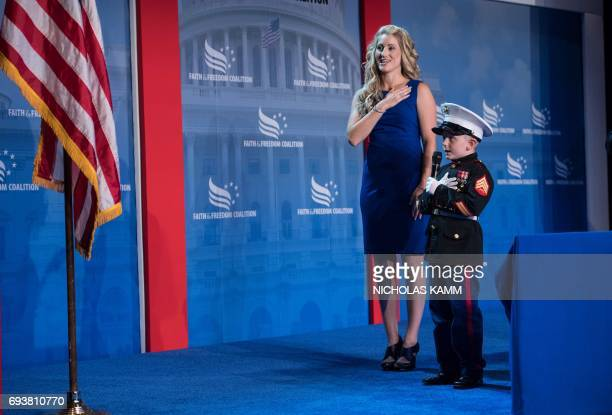 Sixyearold Christian Jacobs says the Pledge of Allegiance with his mother Brittany Jacobs before US President Donald Trump addresses the Faith and...
