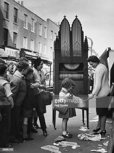 Sixyearold Deborah Burchett hands over her money to Miss Mary Wright outside the Church of Our Most Holy Redeemer in Clerkenwell London in exchange...