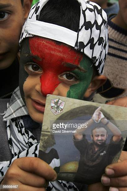 Sixyearold Fatah supporter Fawwas Hammad Sawus holds a campaign photo of Marwan Barghoutti that he keeps in his scarf while campaigning for his...