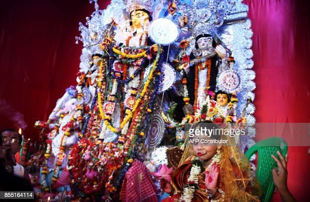 Sixyearold Hindu girl Anushka Chetterjee dressed as the Hindu goddess Durga looks on during celebrations for the 'Durga Puja' festival in Kolkata on...
