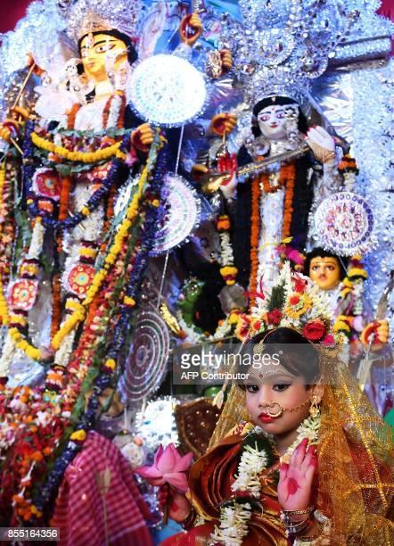Sixyearold Hindu girl Anushka Chetterjee dressed as the Hindu goddess Durga looks on at a 'pandal' for the celebrations the 'Durga Puja' festival in...