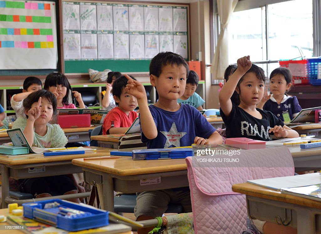 Six-year-old Japanese elemetary student Seishi Nishida (C) raises his hand along with classmates at school in Tokyo on June 11, 2013