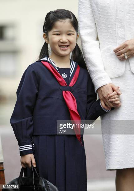 Sixyearold Japanese Princess Aiko accompanied by her mother Crown Princess Masako smiles as she arrives to attend her entrance ceremony at the...