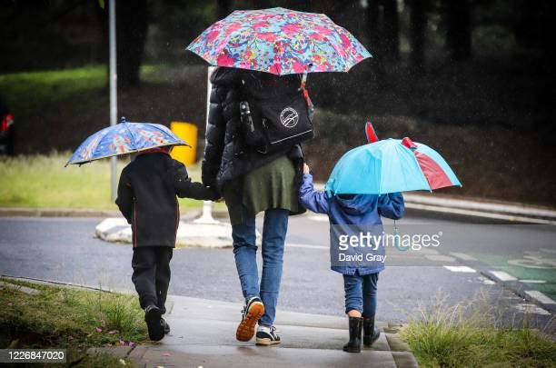 Six-year-old Kaya Atayman walks with his mother Famona and four-year-old brother Arly to school in the suburb of Bondi on May 25, 2020 in Sydney,...