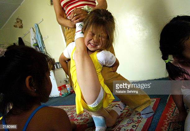 Sixyearold Khulan winces as her leg is stretched behind her neck during a contortion lesson at the Mongolian State Circus July 17 2003 in Ulan Bator...