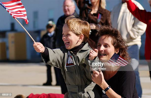 Sixyearold Matthew Mitchell and his mother Dana Mitchell wave American flags as the F14 Tomcat flown by her husband Lt Eric Mitchell taxis to the...