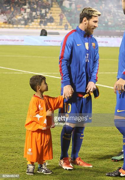 Sixyearold Murtaza Ahmad with Lionel Messi of Barcelona during the Qatar Airways Cup match between FC Barcelona and AlAhli Saudi FC on December 13...