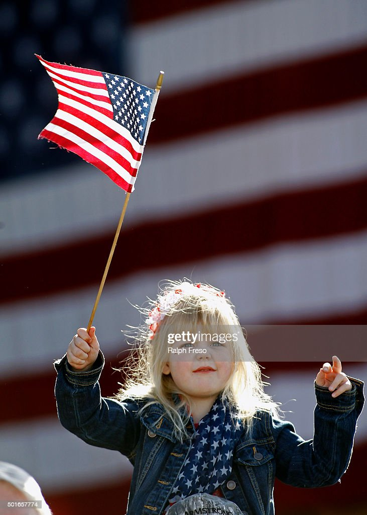 Six-year-old Summer Johnston waves a flag as she waits for the arrival of Republican presidential candidate Donald Trump to a campaign event at the International Air Response facility on December 16, 2015 in Mesa, Arizona. Trump is in Arizona the day after the Republican Presidential Debate hosted by CNN in Las Vegas, Nevada.