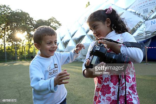Sixyearold Syrian refugee Malaki shows a picture she has just taken with a photographer's camera of fouryearold Syrian refugee Yahya outside of an...