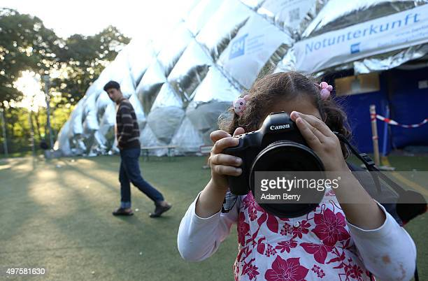Sixyearold Syrian refugee Malaki takes a picture with a photographer's camera outside of an airdome used as a temporary shelter for refugees on...