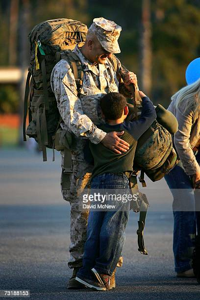 Six-year-old Tyler holds onto his father Gunnery Sgt. Willy Ellerbrock as Marines and sailors of the 1st Marine Logistics Group return home from a...