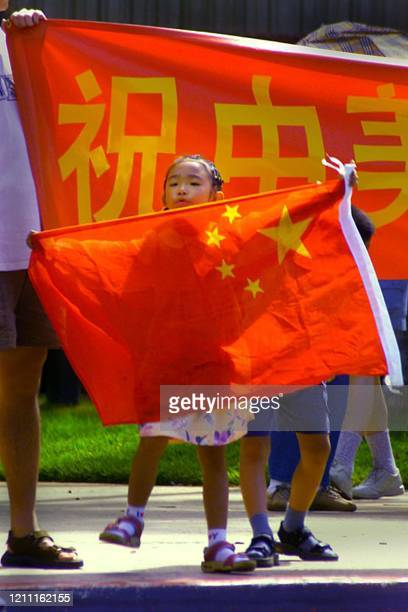 Six-year-old Ya You holds the Chinese flag in anticipation of the arrival of Chinese Vice President Hu Jintao to Honolulu, Hawaii, 27 April 2002....