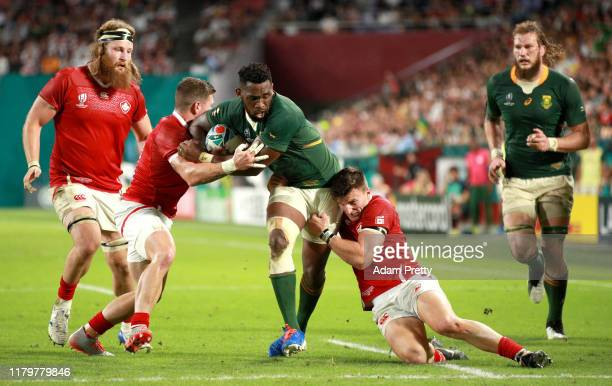 Siya Kolisi of South Africa is tackled by Jamie Mackenzie and Andrew Coe of Canada during the Rugby World Cup 2019 Group B game between South Africa...