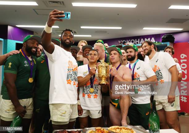 Siya Kolisi of South Africa takes a picture with his team mates and the Web Ellis Cup inside the dressing room following their team's victory against...