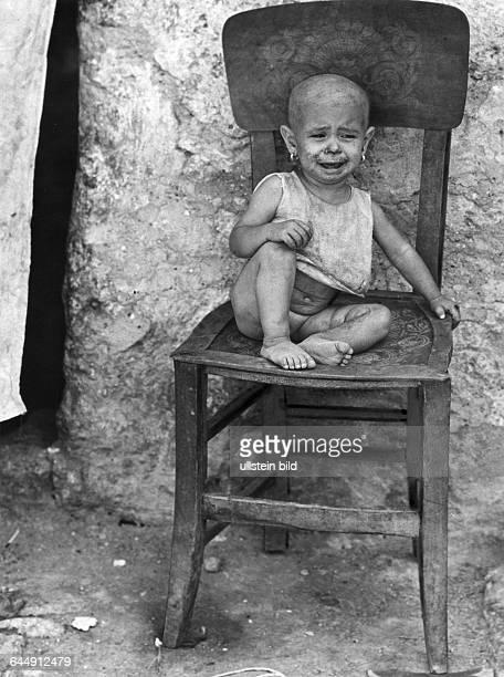 Kind in Palermo verwahrlostes kleines Mädchen sitzt weinend auf einem Stuhl