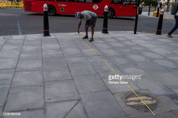 Sizing up proportions and pavement width, a man stretches a measuring tape at Bank in the City of London, in order to measure the possibility of...