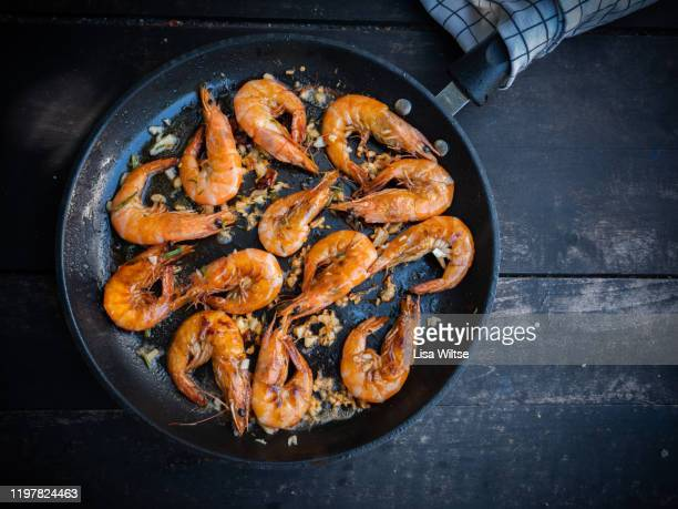 sizzling garlic prawns in a cast iron pan - dark panthera stock pictures, royalty-free photos & images