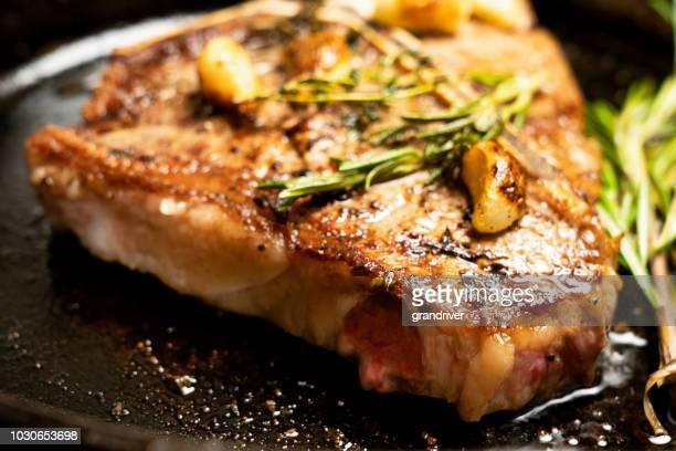 sizzling t-bone steak on a cast iron skillet with herbs and garlic - bistecca alla fiorentina foto e immagini stock