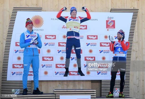 Sjur Roethe of Norway celebrates alongside Alexander Bolshunov of Russia and Martin Johnsrud Sundby of Norway following his win in the Cross Country...