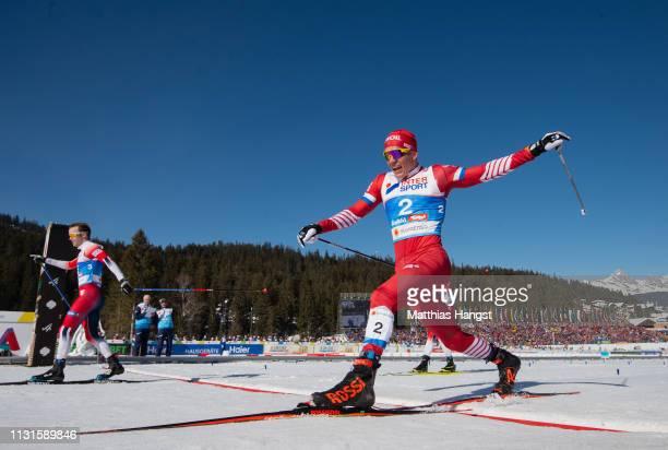 Sjur Roethe of Norway celebrates as he crosses the finish line ahead of Alexander Bolshunov of Russia to win the Cross Country Skiathlon Men 30k race...