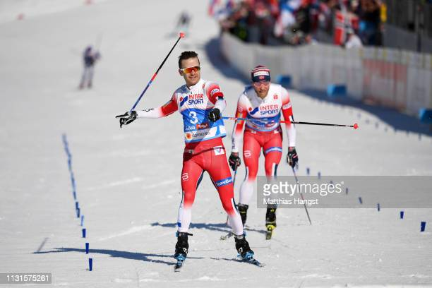 Sjur Roethe of Norway celebrates as he crosses the finish line to win the Cross Country Skiathlon Men 30k race during the FIS Nordic World Ski...