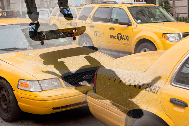 Skate boarding over New York taxis