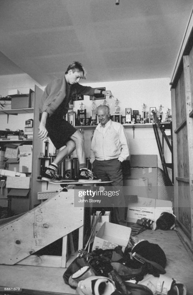 Skateboard champion Tony Hawk (L) practicing tricks in garage with his father Frank (R) watching.
