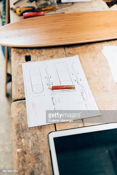 Skateboard, design and tablet in workshop
