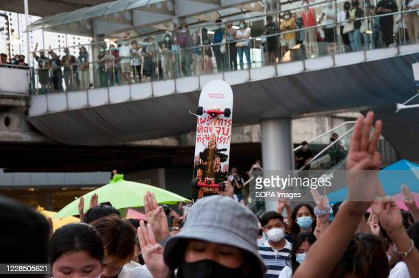 """Skateboard is held up in a crowd with message on the skateboard reading """"The dictator shall perish"""". The group called """"Free Arts"""" held an """"Act si..."""