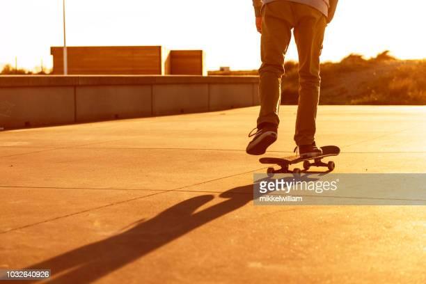 Skateboard rider makes his way forward as the sun sets in the horizon