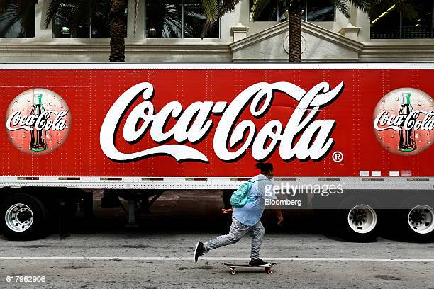 A skateboarded rides past CocaCola Co signage seen on a delivery truck in Miami Beach Florida US on Monday Oct 24 2016 The CocaCola Co is scheduled...