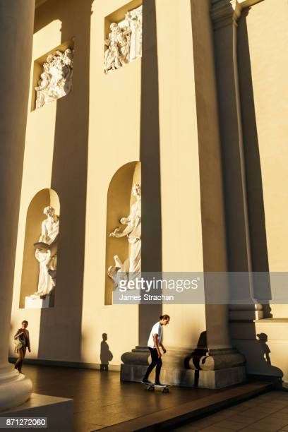 Skateboarder and shadow with passer by in the forecourt of French Classicist Cathedral, Vilnius Cathedral (Skateboarder Model Release), Lithuania (reflects young nation navigating a path against grand history and traditions)
