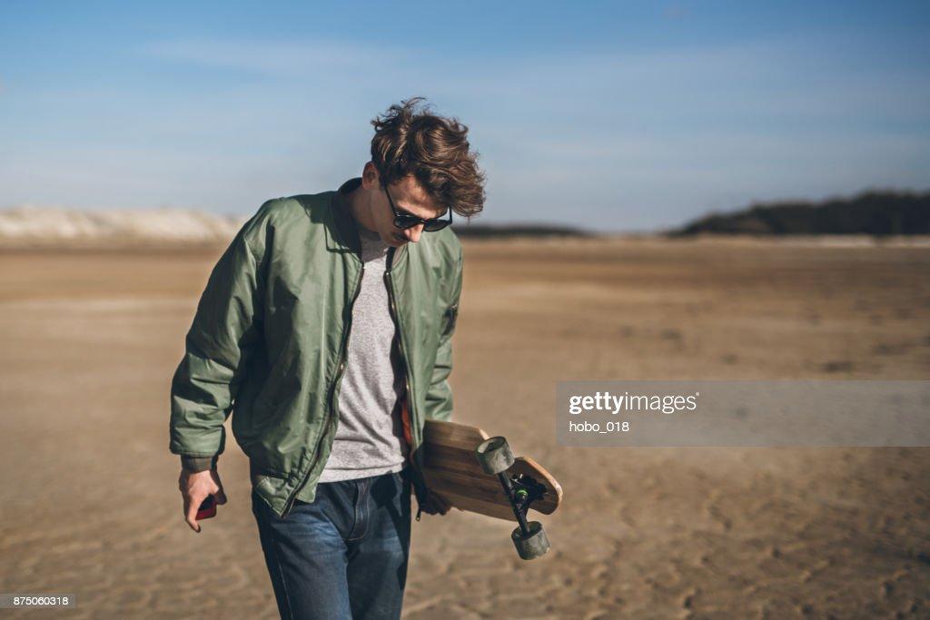 Skateboarder at beach : Stock Photo