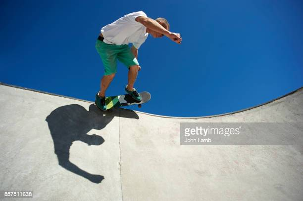 skateboarder at edge of skateboard park bowl. - skating stock pictures, royalty-free photos & images