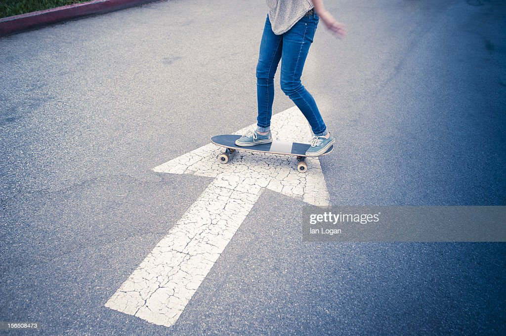Skateboarder crossing an arrow in a parking lot : ストックフォト