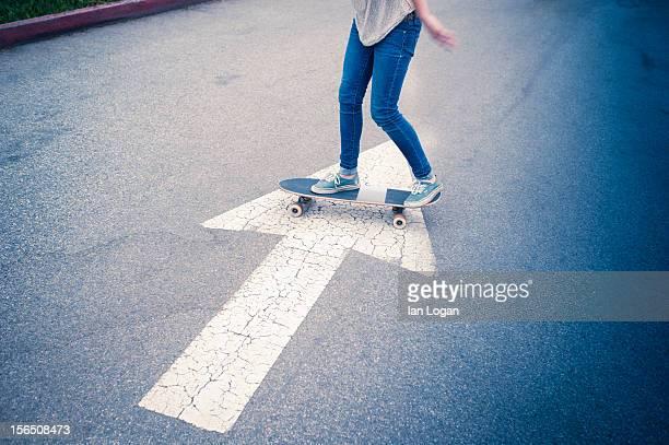skateboarder crossing an arrow in a parking lot - enge jeans stock-fotos und bilder