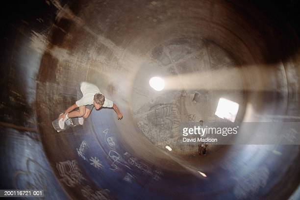 Skateboarder doing half-pipe inside industrial drum