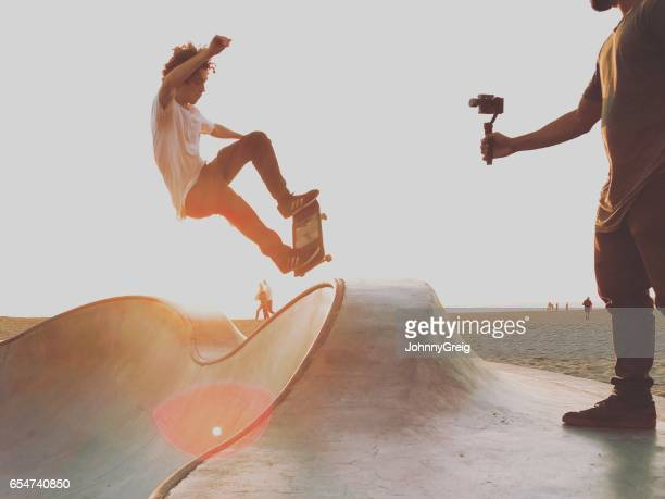 skateboarder doing jump while being filmed - taken on mobile device stock photos and pictures