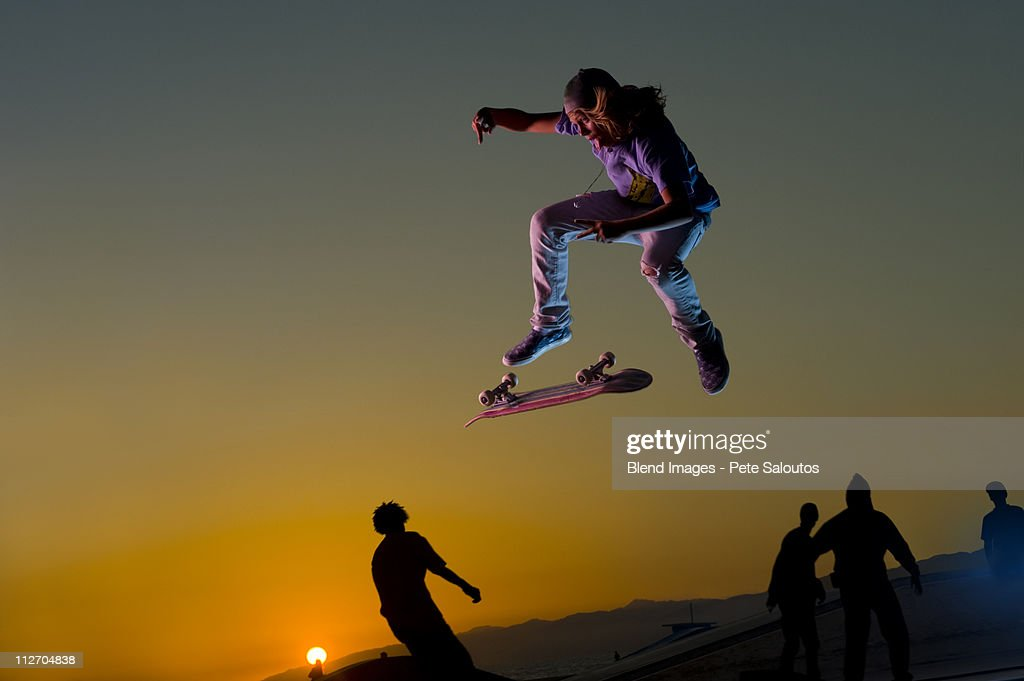 Skateboarder doing stunt in mid-air at sunset : Stock Photo