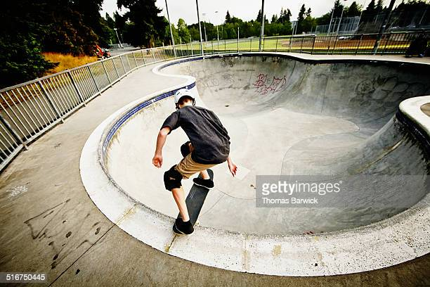 Skateboarder dropping into bowl of skate park