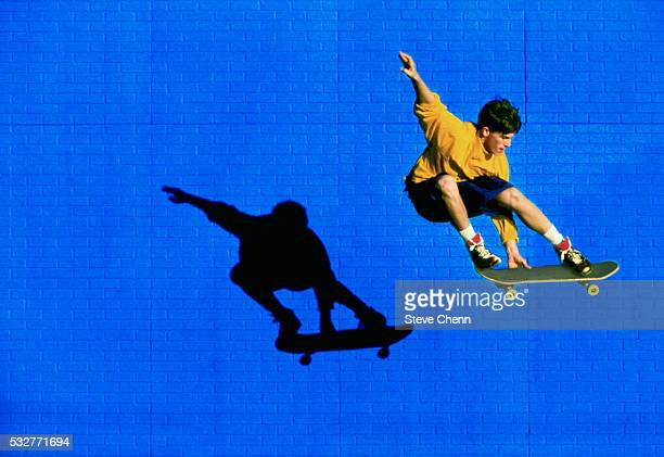 skateboarder flying past blue brick wall - skating stock pictures, royalty-free photos & images