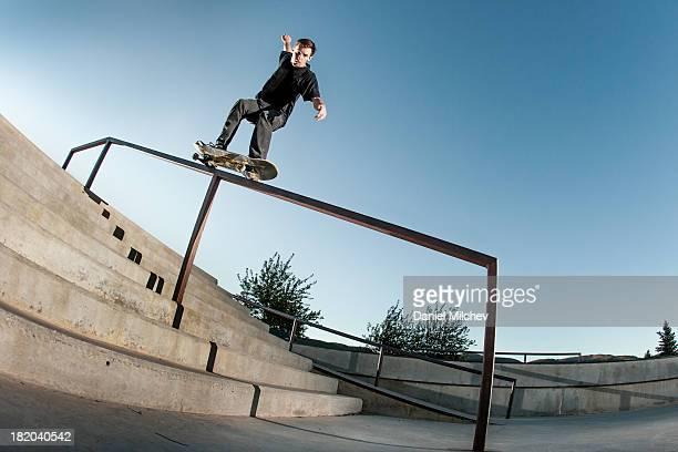 Skateboarder grinding a hand rail.