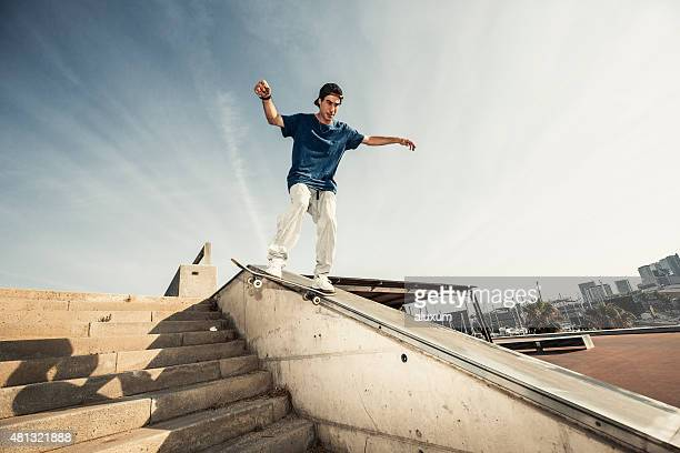 Skateboarder grinding down on concrete wall
