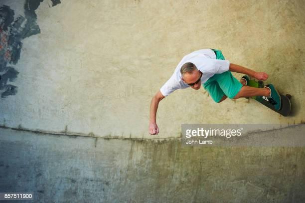 skateboarder high up on skatepark bowl - skating stock pictures, royalty-free photos & images