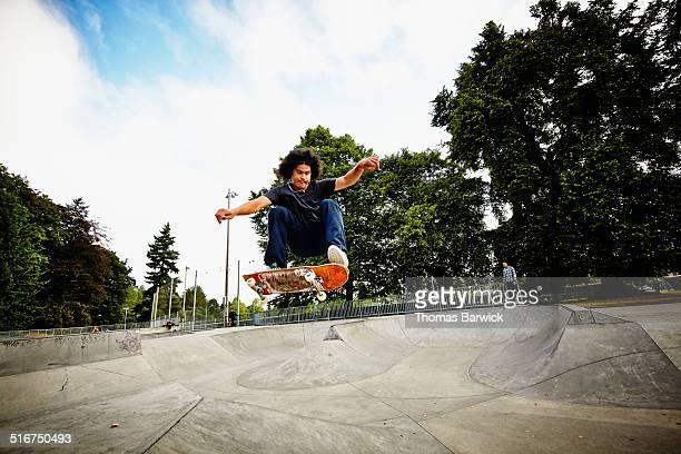 skateboarder in mid air in skate park - skateboard ストックフォトと画像