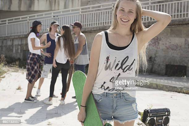 Skateboarder in tank top with wild at heart slogan, friends in background