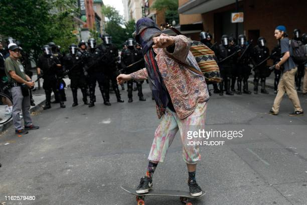 A skateboarder is seen in front of a phalanx of riot police in downtown Portland as hundreds of members of the extreme right including Proud Boys...