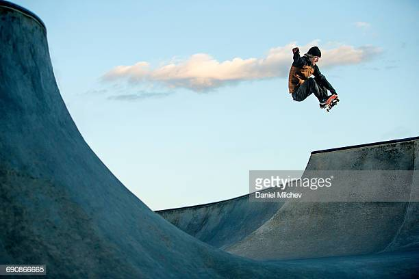 Skateboarder jumping at a skate park.